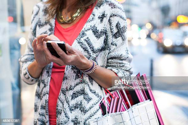 Woman using smartphone while shopping