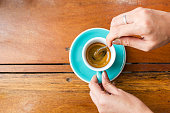 Woman using spoon stir espresso coffee in blue cup. Top view with copy space on wooden table. Food and drink background.