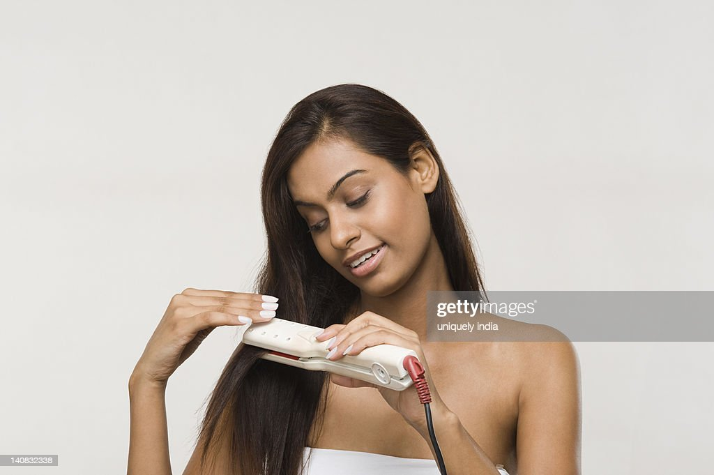 Woman using straightening irons on her hair