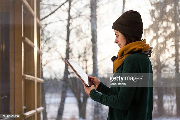 Woman using tablet at home (winter). Helsinki, Finland