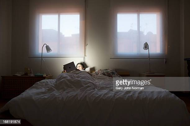 woman using tablet at night in bed
