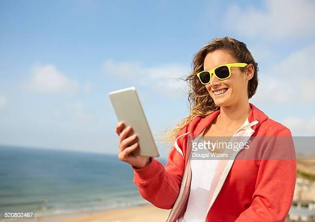 Woman using tablet beside beach