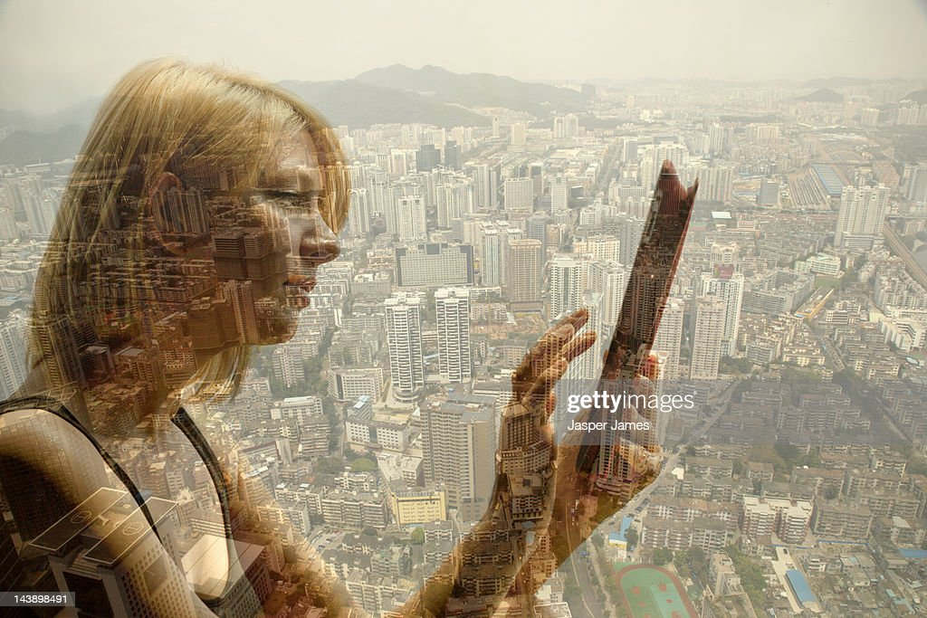 woman using ipad and cityscape : Stock Photo