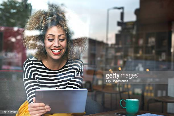 Woman using tablet computer in coffee shop