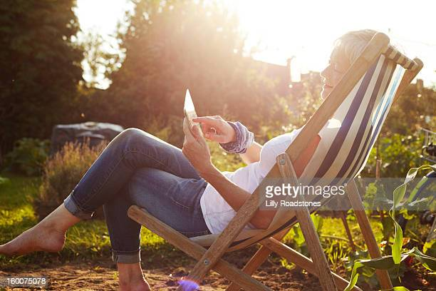 Woman using tablet computer on allotment