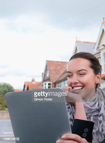 Woman using tablet computer outdoors : Stock Photo