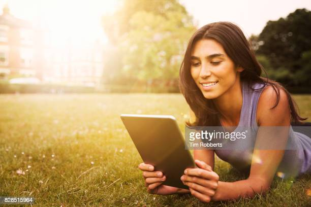 Woman using tablet on grass