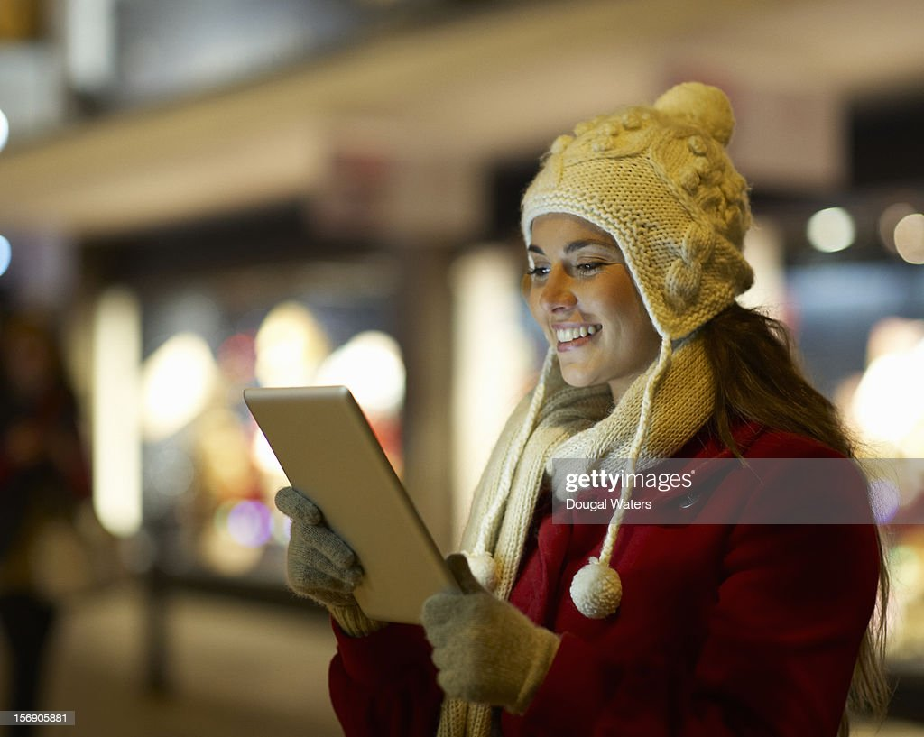Woman using tablet on street at Christmas. : Stock Photo