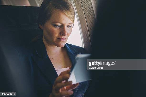 Woman using tablet pc in plane.