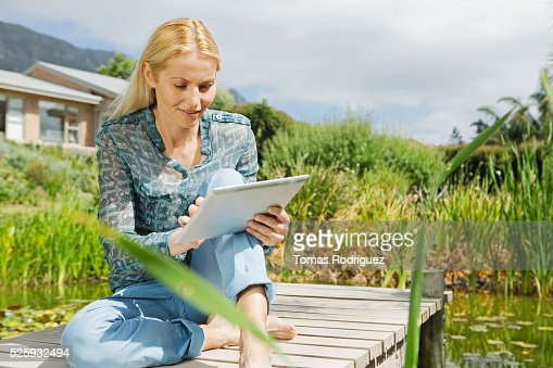 Woman using tablet pc on jetty : Stock Photo