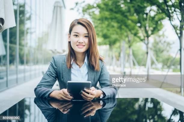 woman using tablet PC while sitting at sidewalk cafe