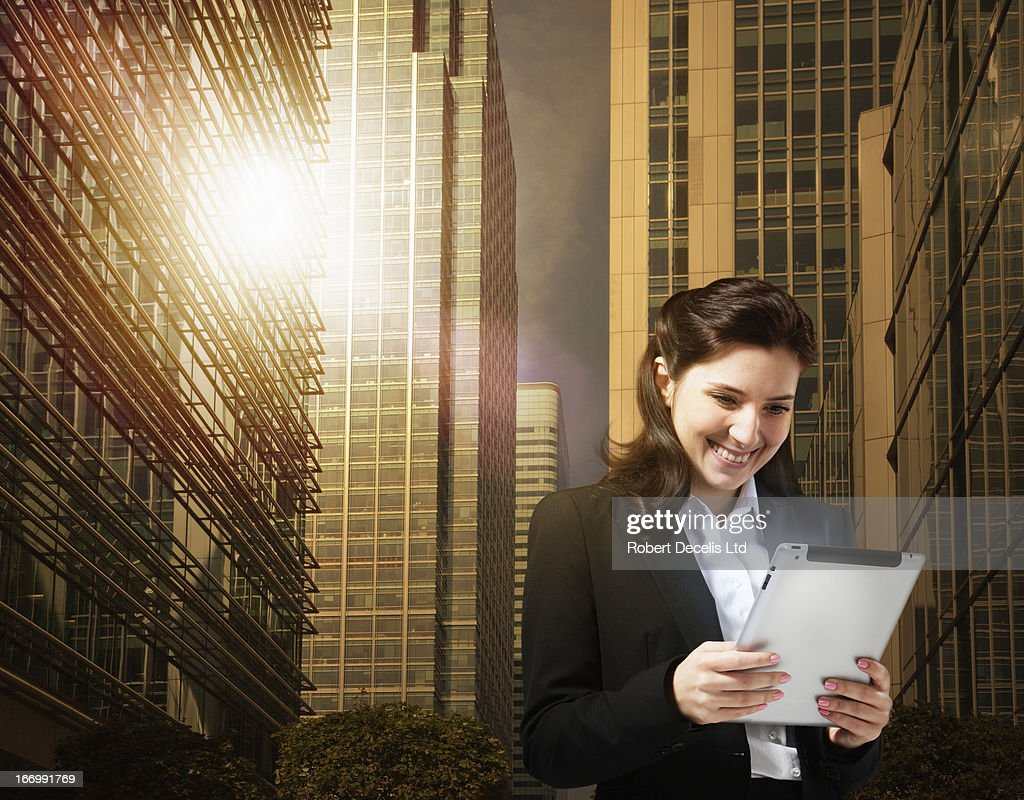 Woman using tablet with city scape behind : Stock Photo