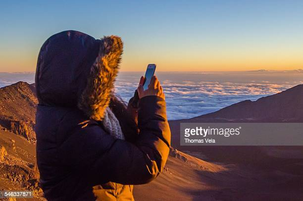 Woman using technology To take a photo from the summit of a volcano
