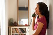 Woman using telephone in hallway