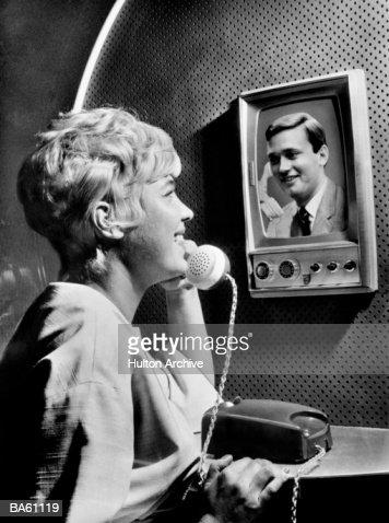 Woman using telephone, talking to man on screen (B&W) : Foto de stock
