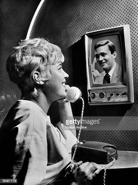 Woman using telephone, talking to man on screen (B&W)