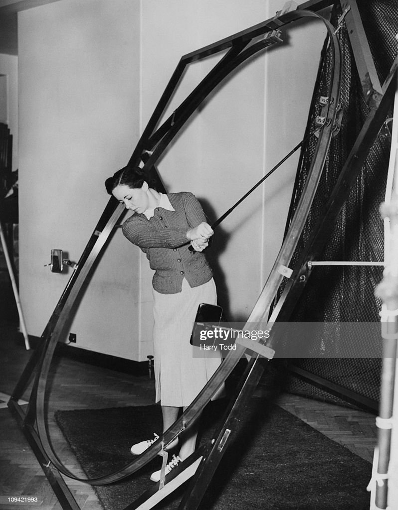A woman using the 'Grooved Swinger' golf training device at Lillywhites Golf School, Knightsbridge, London, 19th July 1939. The device has mirrors attached, so that the golfer can see where their action is at fault when driving.