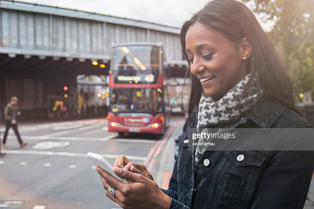 Woman using the new technologies for a taxi in London : Stock Photo