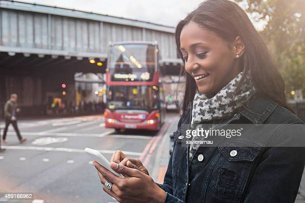 Woman using the new technologies for a taxi in London