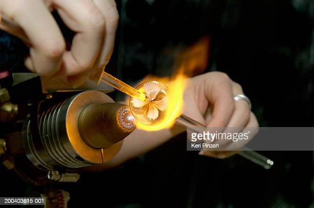 Woman using torch to make glass marble