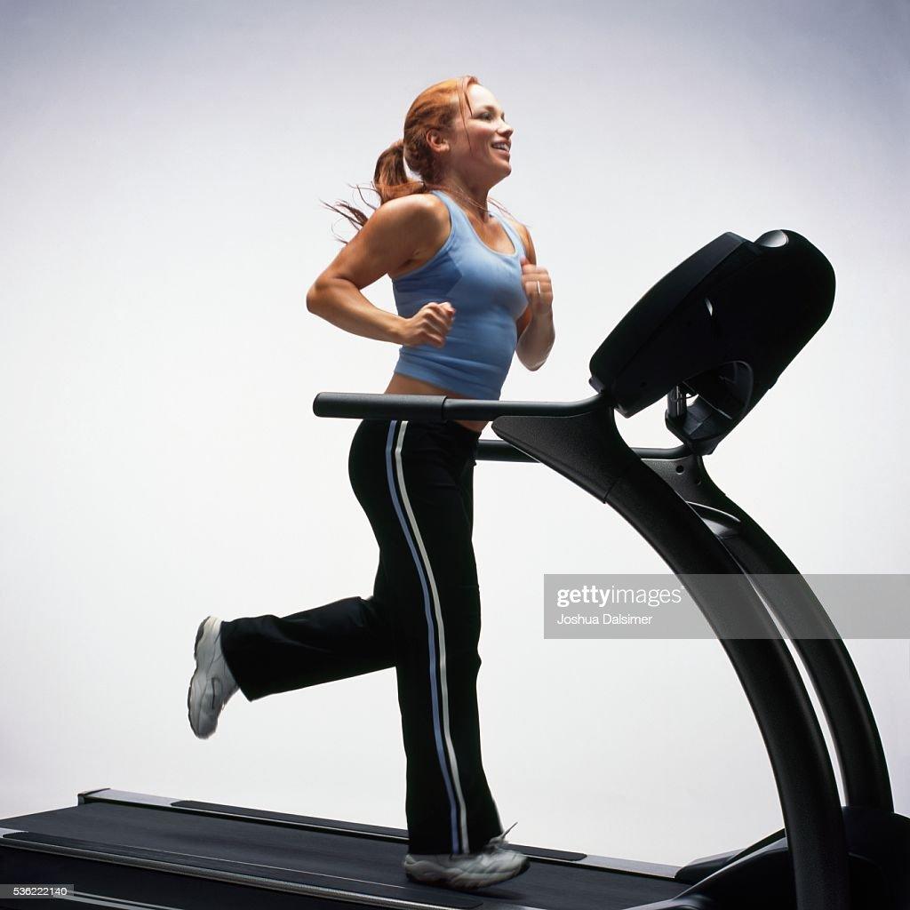Woman using treadmill : Stock Photo
