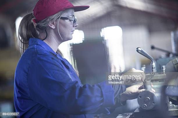 Woman using Vernier caliper in workshop