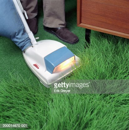 Woman vacuuming artificial grass, low section : Stock Photo