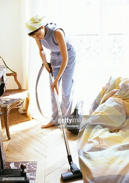 Woman vacuuming, full length