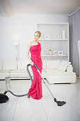 Woman vacuuming in evening gown