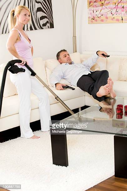 Woman vacuuming, man lying on a sofa watching television