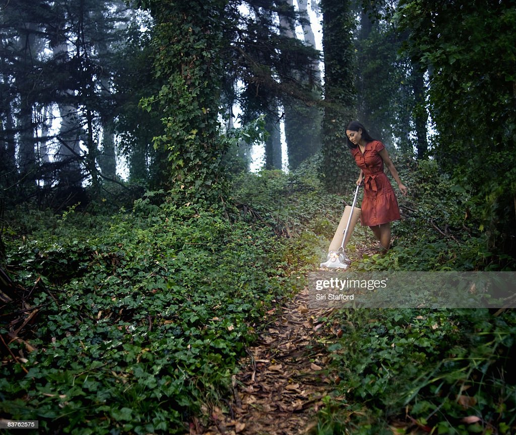 Woman vacuuming path in ivy covered forest : Stock Photo
