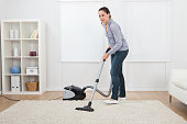 Full length of young woman vacuuming rug at home