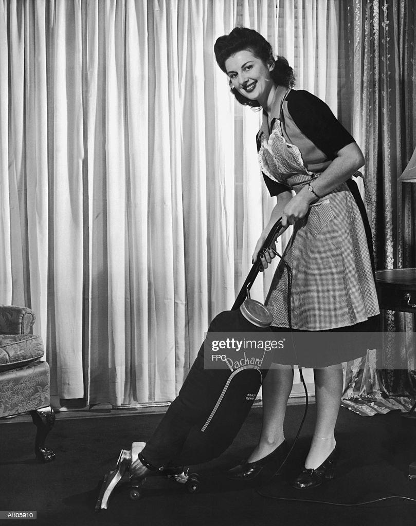 Woman vacuuming, smiling, portrait (B&W) : Stock Photo