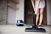Woman vacuuming the floor. Close-up on vacuum cleaner.