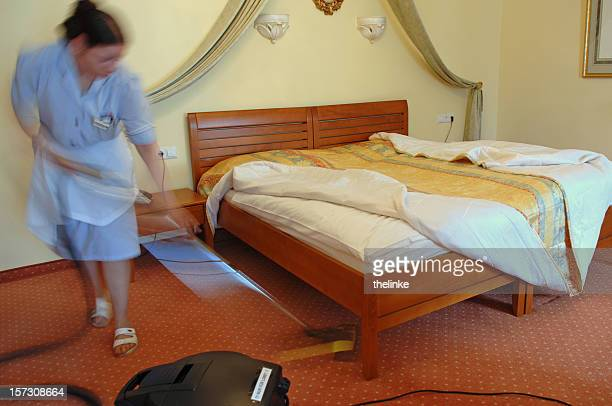 Woman vacuuming the hotel room