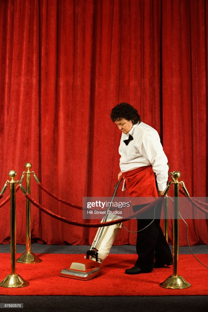 Woman vacuuming the red carpet : Stock Photo