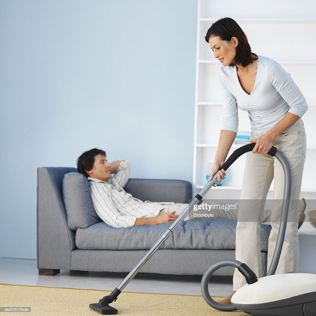 Woman vacuuming while man relaxes on a sofa : Stock Photo
