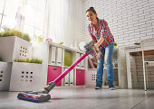Beautiful young woman makes cleaning the house. Woman vacuums the floor