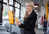 Young woman validating electronic ticket in public transport