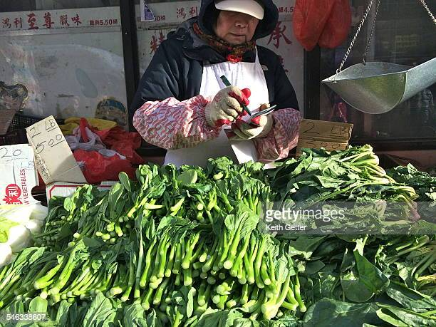 A woman vendor stands behind her outdoor food and vegetable stall in Chinatown Manhattan NYC with lots of green vegetables for sale January 25 2015