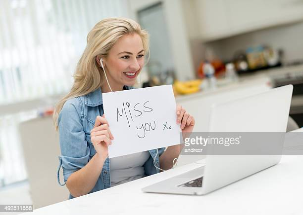Woman video chatting and holding a miss you sign
