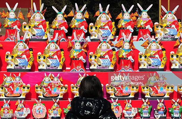 A woman views a display featuring mythical Beijing folk icon 'Lord Rabbit' figurines on display in front of a taoist temple on the first day of the...