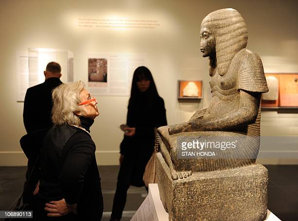 A woman views a stone statue 'Haremhab as a Scribe' New Kingdom Dynasty 18 reign of Tutankhamun or Aya ca 1328�1316 BC on display Novermber 15 2010...