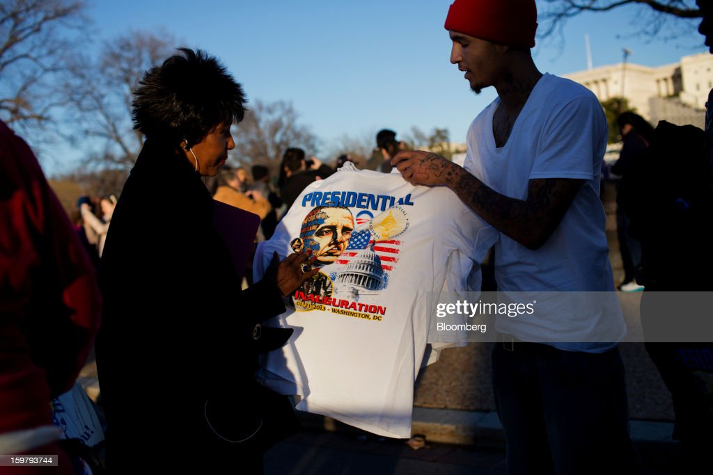A woman views a U.S. President Barack Obama t-shirtvendor Dwayne Quattlebaum, right, displays for sale ahead of the presidential inauguration in Washington, D.C., U.S., on Sunday, Jan. 20, 2013. As he enters his second term Obama has shed the aura of a hopeful consensus builder determined to break partisan gridlock and adopted a more confrontational stance with Republicans. Photographer: Victor J. Blue/Bloomberg via Getty Images