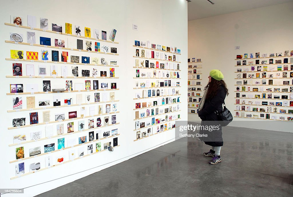A woman views an exhibition of 2,700 post-card size artworks at the Royal College of Art on March 22, 2013 in London, England. The Artworks, including work by Julian Opie, Paula Rego, David Bailey, Sir Paul Smith and Nick Park will go on sale on Saturday 23 March from 7am, costing just £45 each. The creators of the postcards remain anonymous until they are bought and the signature is revealed on the back. The RCA are hoping to raise over £120,000 from this year's sale.