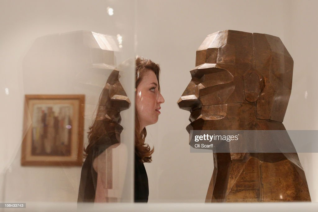 A woman views artwork by Eduardo Paolozzi entitled 'Large Bronze Head' in the 'Perfect Place to Grow' exhibition at The Royal College of Art in celebration of their 175th anniversary on November 15, 2012 in London, England. The Royal College of Art's major exhibition, 'The Perfect Place to Grow', features over 350 works of art and design by RCA graduates and staff including: Henry Moore, Tracey Emin and David Hockney. The RCA is the world's oldest art and design university in continuous operation and it currently educates 1,200 postgraduate students from 55 different countries.