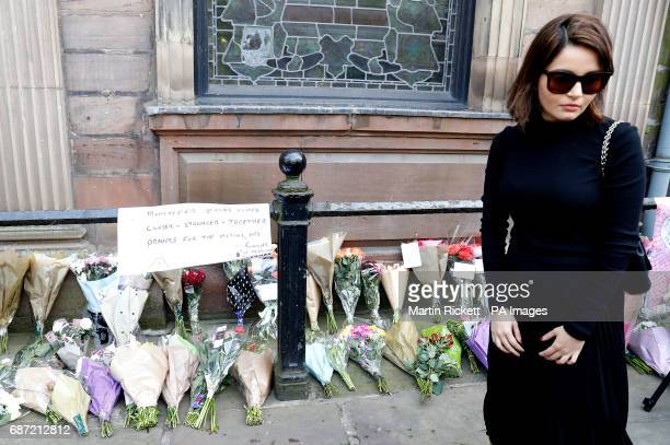 A woman views floral tributes left outside St Ann's Church Manchester following the Manchester Arena bomb attack