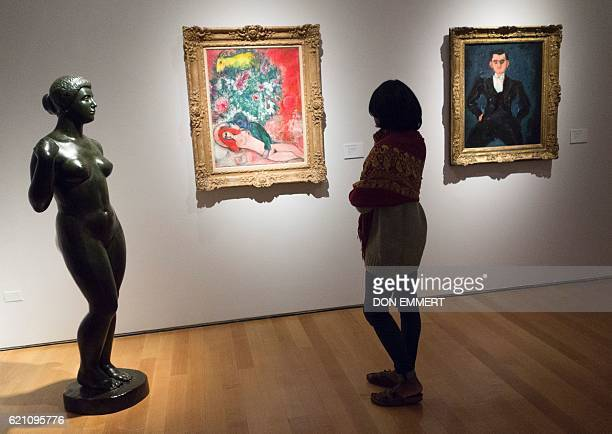 A woman views 'Nu rose ou Amoureux en rose' by Marc Chagall and 'Le garcon d'etage' by Chaim Soutine on November 4 2016 in New York during a press...