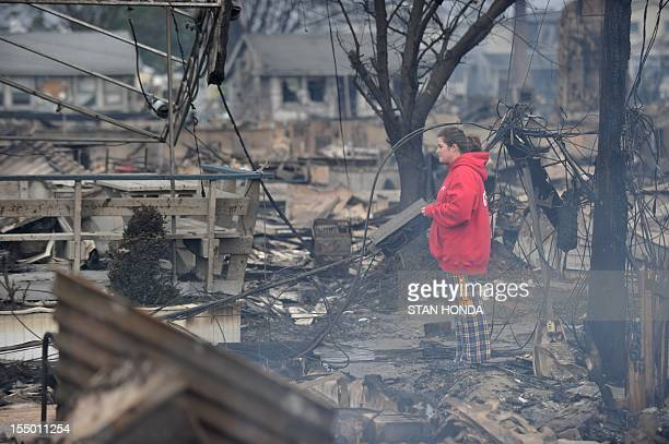 A woman views still smoldering damage in a neighborhood in the Breezy Point area of Queens in New York on October 30 2012 after fire destroyed about...