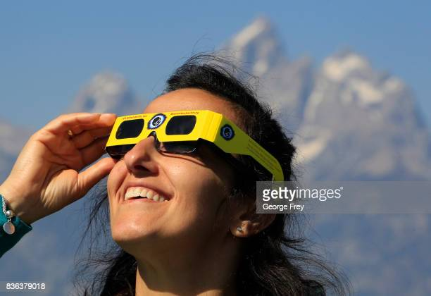 A woman views the solar eclipse in the first phase of a total eclipse in Grand Teton National Park on August 21 2017 outside Jackson Wyoming...